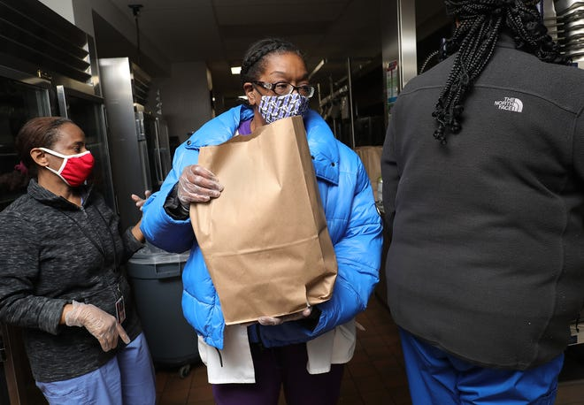 Food-service employees from Columbus City Schools pass out meal packs at Linden-McKinley High School last week to help get families through winter break. The workers, from left, are Elsa Asgede, Carmentta Weaver and Camica McSwain.