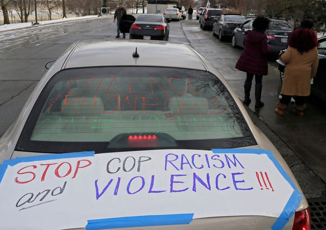 A sign asking for an end to police racism and violence decorates a car's trunk before a caravan demanding justice for Andre Hill left Genoa Park in Downtown Columbus, Ohio, on December 27, 2020. Hill was fatally shot by Columbus police officer Adam Coy on December 22, 2020, outside a home on the Northwest Side.
