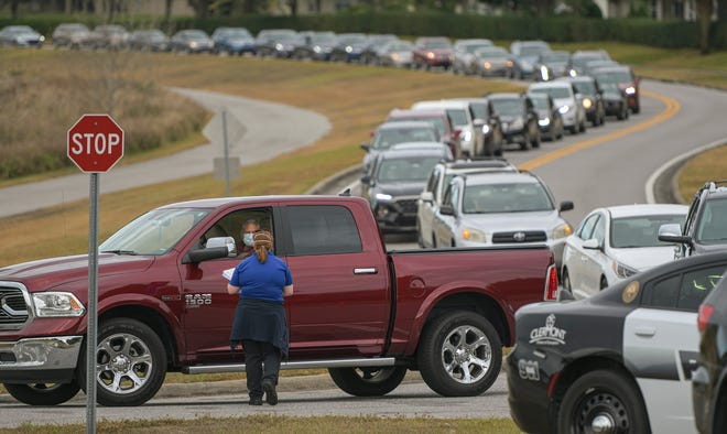 Cars line up on Wednesday on Oakley Seaver Drive as patients wait for their turn at COVID-19 vaccines at Cooper Memorial Library in Clermont