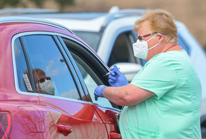 A health care worker prepares to give a dose of the Moderna vaccine to a patient on Wednesday at a distribution site at Cooper Memorial Library in Clermont.