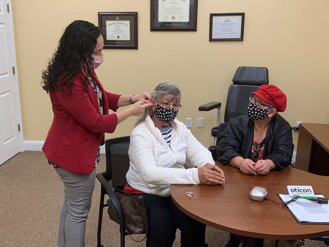 Dr. Kristen Weinbaum fits contest winner Marlene Arbelaez for her new hearing aids at Precision Hearing in Clermont.
