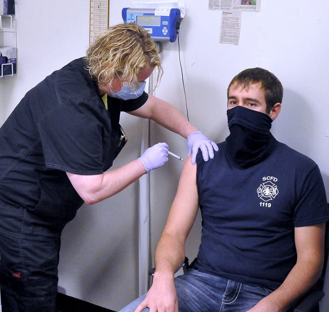 Megan Steiner of the Wayne County Health Department administers the first of two COVID-19 vaccine doses to South Central firefighter Rustyn Shetler.