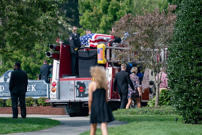 The body of Henderson County sheriff's deputy Ryan Hendrix is carried on a fire truck from Mud Creek Baptist Church to Forest Lawn Cemetery following his funeral service on Sept. 18, 2020. Hendrix died in the line of duty.