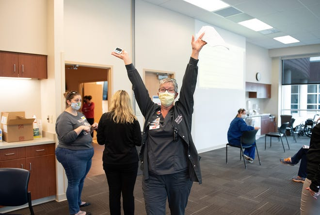 Valerie Cooper, manager of nursing operations at Abraham Lincoln Memorial Hospital, celebrates after receiving her first of two vaccinations for the novel coronavirus. The hospital began administering the vaccine to its frontline healthcare workers last week. The vaccine is voluntary.