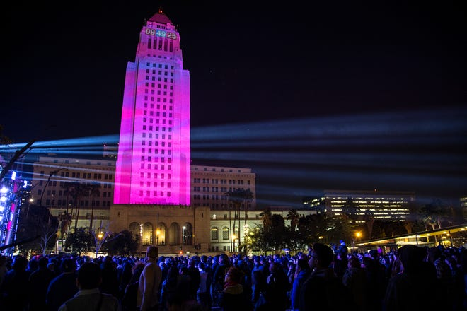 Los Angeles City Hall on Dec. 31, 2015, is lit up in pink with the countdown clock illuminated at the top as revelers enjoy live music during New Year's Eve celebration at Grand Park in Los Angeles. (Gina Ferazzi/Los Angeles Times/TNS)