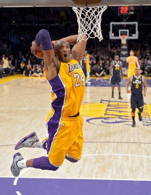 Former Los Angeles Lakers guard Kobe Bryant goes up for a dunk during the first half of an NBA basketball game against the Utah Jazz in Los Angeles on Jan. 25, 2013. Bryant is the game's fourth-leading scorer. He spent 20 years with the Los Angeles Lakers, 18 as an All-Star and won five titles. Then came the helicopter crash in the fog-shrouded California hills that reverberated across sports earlier this year.