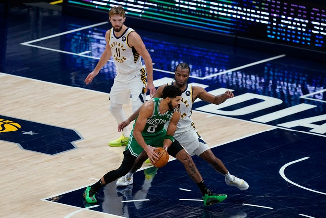 Celtics forward Jayson Tatum (front) goes to the basket against Pacers forward T.J. Warren (right) during the second half of Boston's 116-111 victory over Indiana in Indianapolis.