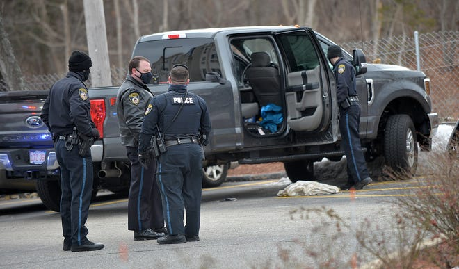 Police examine a green Ford pickup truck in connection to arrests made at Motel 6 in Framingham, Dec. 30, 2020.