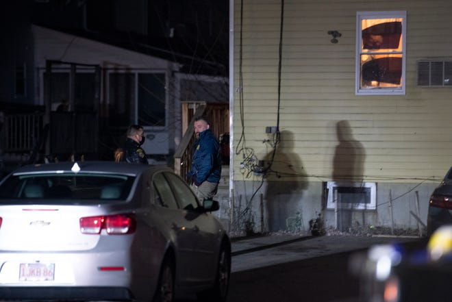 Framingham police officers talk outside the building after a man was shot inside a home on Brackett Road on Tuesday night, Dec. 29, 2020.