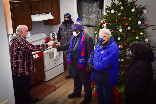 Sporting a Buffalo Bills jacket and scarf, Utica resident John Smythe receives the keys to his very first house provided by the Rescue Mission of Utica.