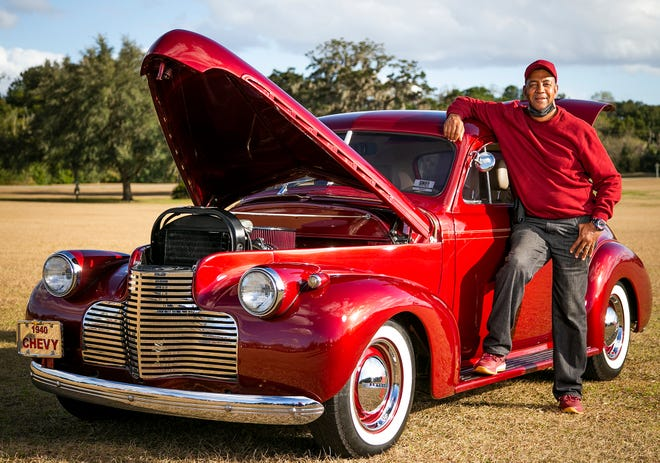 """Wayne Tanner leans on this 1940 Chevy coupe, which he purchased fully restored from the owner in St. Augustine. """"After someone spends $80,000, I come in and buy it for $20 or $30,000,"""" Tanner said."""
