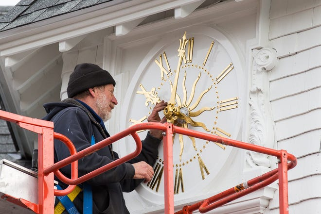 David Graf, historic clock restoration expert puts the finishing touches Wednesday, Dec. 30, 2020, on the newly installed clock face at Carey Cottage in Portsmouth.