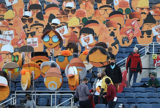 Fans walk in front of Cheez-It fan head icons placed in seats before the start of the Cheez-It Bowl college football game of Miami versus Oklahoma State at Camping World Stadium in Orlando on Tuesday, December 29, 2020, (Stephen M. Dowell/Orlando Sentinel)