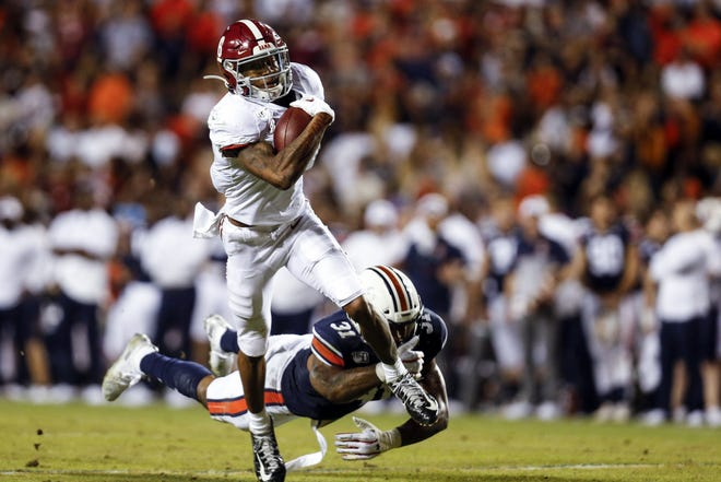 Alabama wide receiver DeVonta Smith catches a pass as Auburn linebacker Chandler Wooten tries to tackle him (Butch Dill, AP)