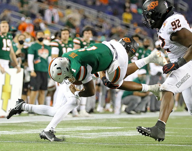 Miami Hurricanes quarterback D'Eriq King (1) is injured after a tackle by Oklahoma State Cowboys safety Tre Sterling (3) in the second quarter during the 2020 Cheez-It Bowl at Camping World Stadium in Orlando on Tuesday, December 29, 2020.