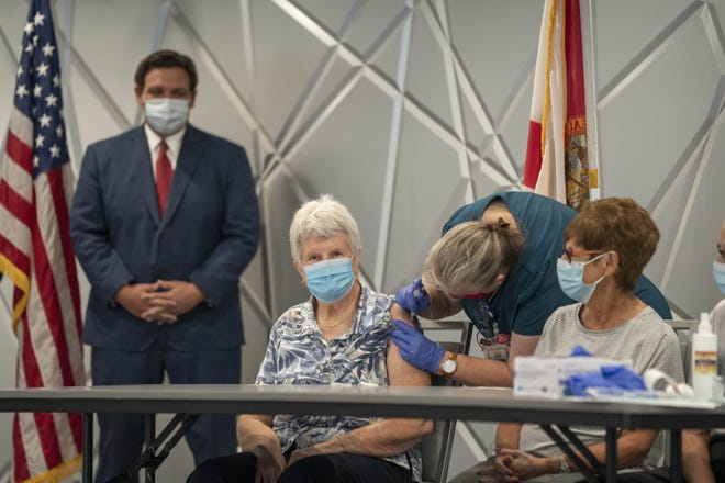 Florida Governor Ron DeSantis, left watches Jessica Brown, 77, receive the Moderna COVID-19 vaccine from nurse Sherry Phillips at the King's Point clubhouse in Delray Beach, Fla. Wednesday, Dec. 30, 2020.