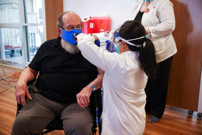 U.S. Air Force Veteran Robert Aucoin, 78, receives a COVID-19 vaccine dose at the Soldiers' Home in Holyoke, Mass., Tuesday.