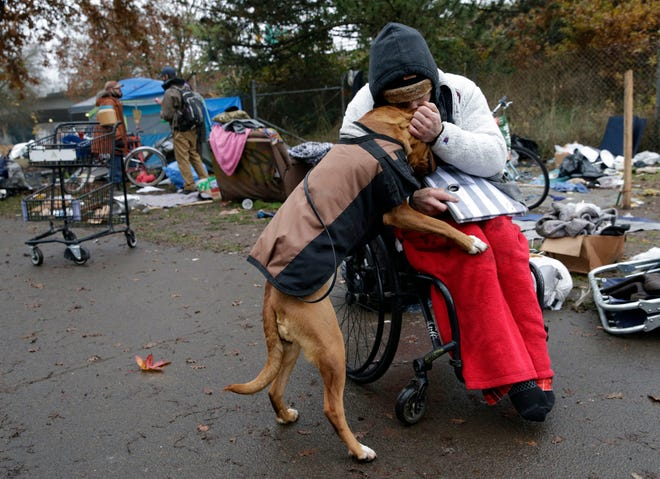 Ritchie Valentine hugs his dog, Boot, as he prepares to move from his tent site on Jefferson Street on Dec. 1 in Eugene, Oregon. Valentine has been paralyzed for about five years after an accident. He has been homeless off and on during that time and has been on the street for about four months.