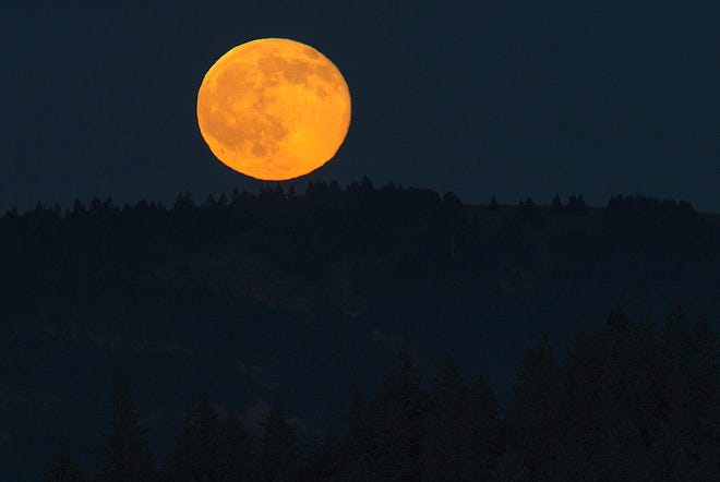 A Strawberry Moon rises over the Willamette Valley as seen from Skinner Butte in Eugene, Oregon in 2016.