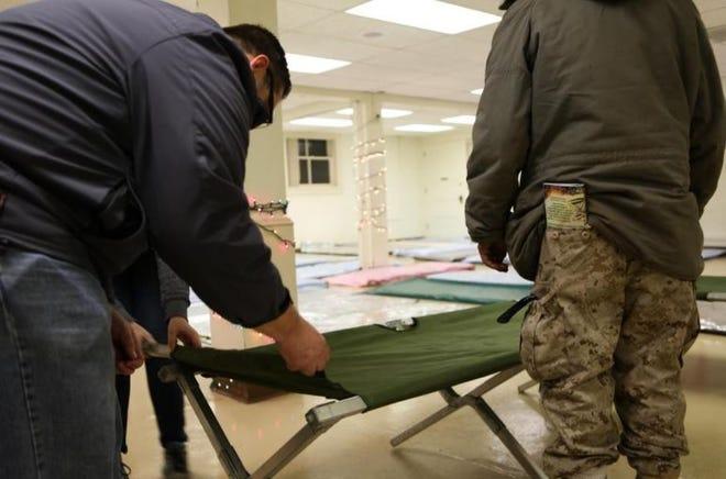 Volunteers set up cots and mats at an Egan Warming Center site.