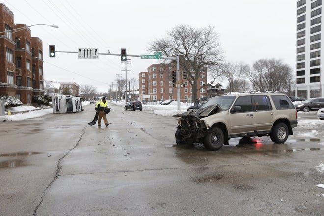 A police officer removes debris from the intersection of North Main and Whitman streets after a crash on Wednesday, Dec. 30, 2020, in Rockford.