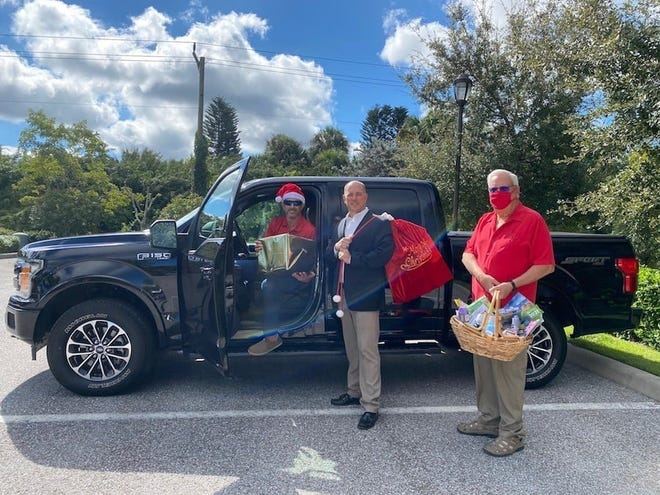 """R. G. """"Kelly"""" Caldwell Jr., CEO/president of Caldwell Trust Co., carries a Santa-style bag of donations collected by the company and its staff for the Holiday Drive sponsored by Meals on Wheels of Sarasota. Scott Antritt, vice president and trust officer, in the truck, and the Rev. Chris Gray, board member, hold other donations for the Holiday Drive."""