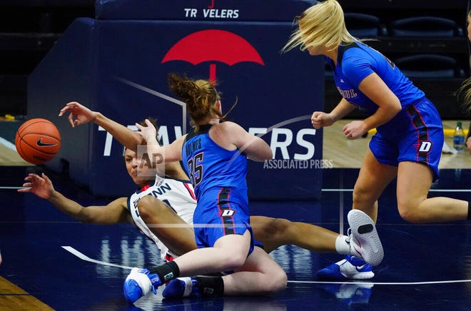 Connecticut forward Olivia Nelson-Ododa passes the ball as DePaul Blue Demons guard Kendall Holmes (35) defends during the first half of an NCAA college basketball game Tuesday, Dec. 29, 2020, in Storrs, Conn.