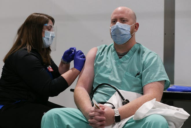 Andrew Barnes, a nurse practitioner in the emergency room at Stormont Vail Hospital, receives the vaccine surrounded by staff and local media on Dec. 16 at Stormont Vail Events Center.
