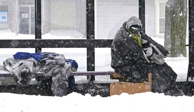 A homeless man takes shelter at a bus stop during a snowstorm on Dec. 17 in Lawrence.