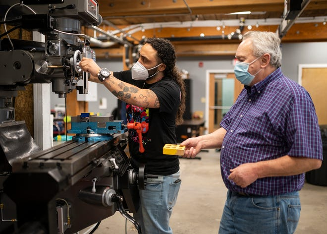 Instructor Mike Hurley, right, and Jamie Powell work on a CNC milling machine at the Blackstone Valley Education Hub.