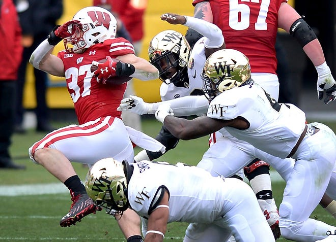 Wake Forest defenders converge on Wisconsin running back Garrett Groshek, left, during Wednesday's Duke's Mayo Bowl.