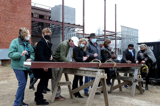 Those attending the Art on Main Topping Off Ceremony take the opportunity to sign the cross beam being raised, Tuesday, Dec. 29, at the new Center for Art & Education Arts on Main center, 414 Main Street.