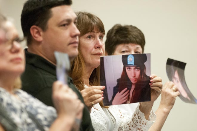 """In this 2016 file photo, Lorraine Sherzer (center) holds a photo of her late daughter, Bodhisattva """"Bodhi"""" Sherzer-Potter, 16, in a Victorville, Calif. courtroom. Sherzer-Potter and her boyfriend, Christopher """"Cody"""" Thompson, 18, were murdered in an abandoned military bunker in 2008."""