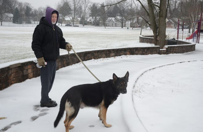 The walk was sloppy Wednesday morning for Robert Gault and his dog, Jack, after snow and rain beginning Tuesday night. They were out for their daily walk in Battle Creek's Piper Park.  (Trace Christenson/The Enquirer)