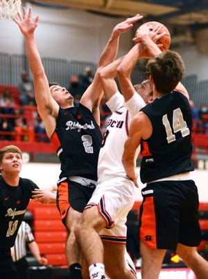 Gabe Tingle, left, and Dalton Patterson go up for a block on Nathan Fauver during the first half of Ridgewood's 51-48 win against host Coshocton on Tuesday night at The Wigwam.