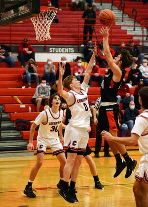 Coshocton's Zach Jennings, left, tries to block the shot of Ridgewood's Dalton Patterson in a game from earlier this season. Patterson made first team All-IVC South Division.