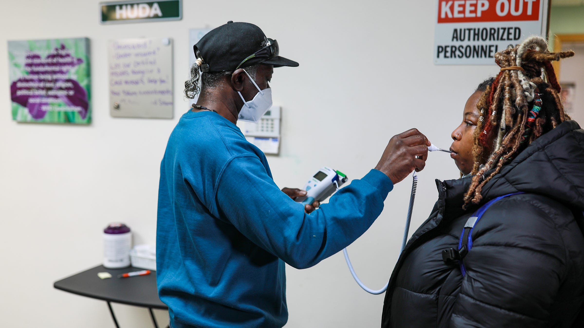 Building Manager Donald Ford, 67, of Detroit checks the temperature of Nikolette Barnes, 34, of Detroit after entering Health Unit on Davison Avenue (HUDA) free clinic in Detroit for COVID-19 precautions on Tuesday, Dec. 29, 2020.