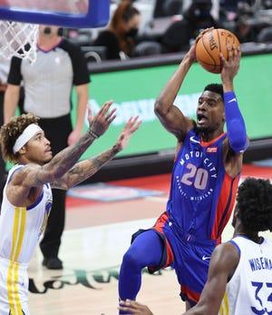 Josh Jackson dari Pistons mencetak gol atas Kelly Oubre Jr dari Warriors pada kuarter kedua.