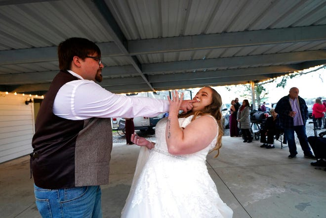 Emily dan Taylor Pascale dengan bercanda berbagi kue pernikahan mereka.