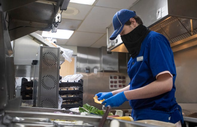 An employee works in the kitchen at a fast-food restaurant in Fort Collins, Colorado. Millions of workers in fast food and other low-paying sectors would get a raise if the minimum wage is increased to $15 an hour, as proposed by President Joe Biden. Many states set their own minimum wage, but it cannot be lower than the federal wage.