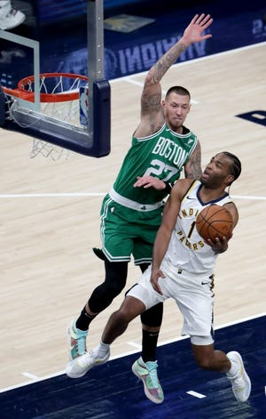 Boston Celtics center Daniel Theis (27) tries to block a shot by Indiana Pacers forward T.J. Warren (1) on Tuesday, Dec. 29, 2020, during a game at Bankers Life Fieldhouse in downtown Indianapolis.