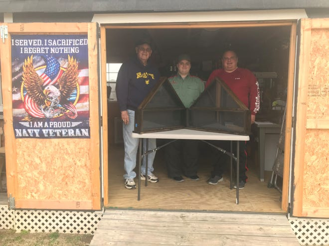 Jacob Smith (middle) shows off a couple of the flag display cases he made with his grandfather Ronnie Hubbard (left) and his father Jason Smith (right). The cases were the project for his Freedom Award in Trail Life USA and donated 20 of them to the American Legion in Jackson.
