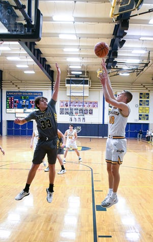 Watkin's Trace Hartman attempts to block Cameron Roudabush's shot Tuesday night at LHS. The Golden Gales defeated the Warriors 70-46.