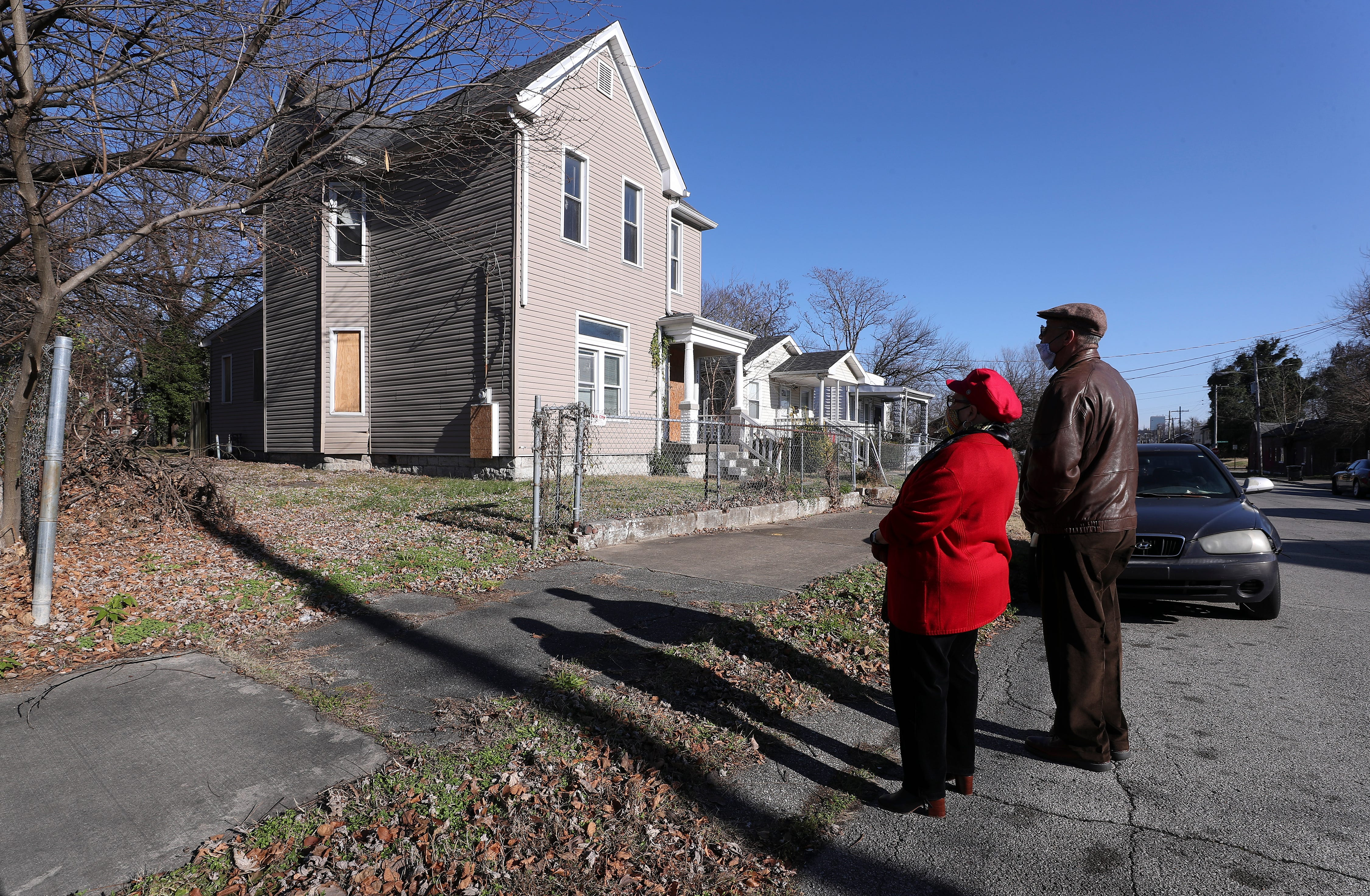 Former educator Deanna Shobe Tinsley, left, and her husband Max Tinsley stop to take a look at her childhood home on Cedar Street in west Louisville. Dec. 22, 2020.