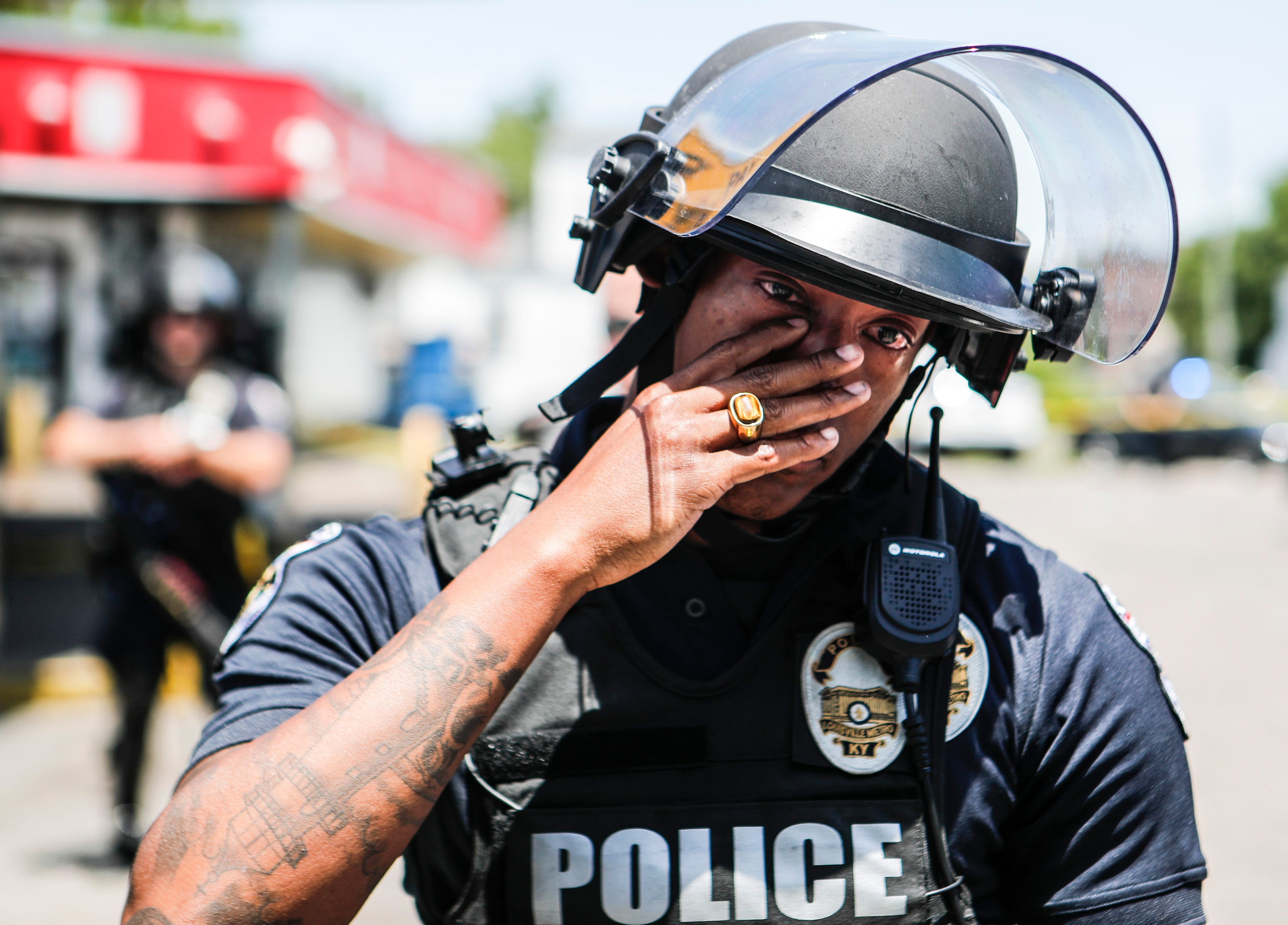 LMPD officer Christian Lewis wipes tears away after hugging a few citizens as hundreds gathered to protest the death of David McAtee, a beloved BBQ owner who was shot and killed amid gunfire by LMPD and Kentucky National Guard early Monday morning near 26th and Broadway in West Louisville. June 1, 2020