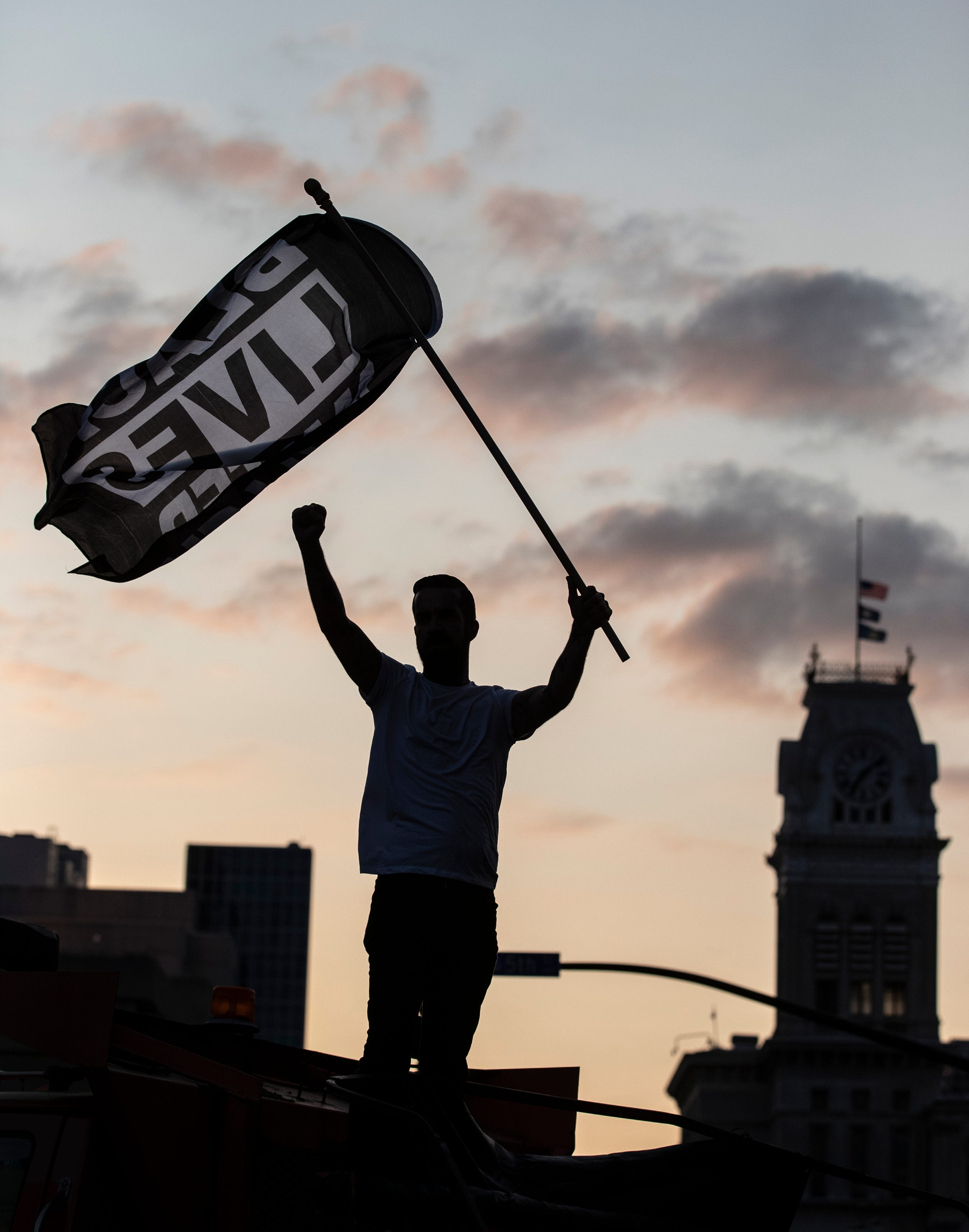 Dylan O'Donoghue stood atop a barricade at Fifth and Jefferson Streets in Louisville, Kentucky and waved a Black Lives Matter flag. Protesters marched through the streets for another night, demonstrating for justice for the late Breonna Taylor. Sept. 26, 2020.
