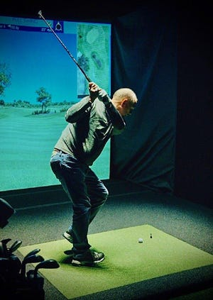 Phil Hughes, father of the owners of Germantown's Stix Golf, Ryan and Daniel, uses a golf simulator at the facility.