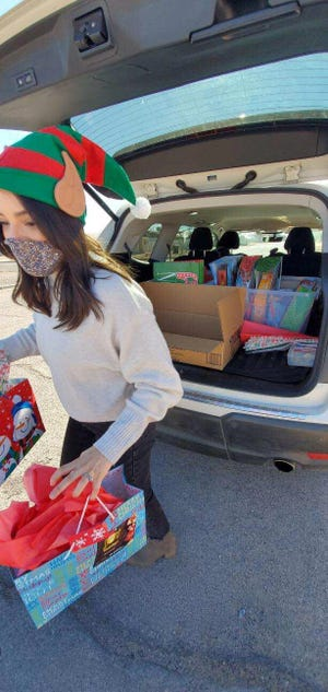 Play Sharity Board Member Cynthia Benting loaded gifts for delivery.