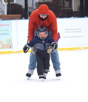 James Goff gets his son Theo, 2, up and ice skating on Dec. 30, 2020 at Farmington's Riley Park Ice Rink.