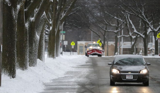 """A motorist drives along Wilson Avenue with plates that say """"FLBOUND"""" probably would rather be where it is warmer, Wednesday, December 30, 2020, in Sheboygan, Wis."""
